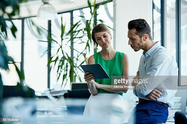 business people using digital tablet in office - groene kleuren stockfoto's en -beelden
