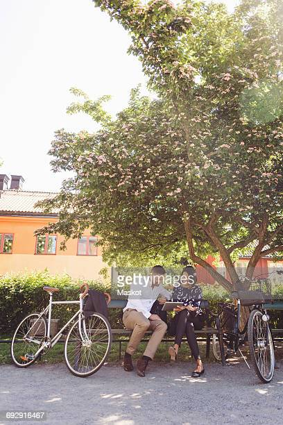 Business people using digital tablet while sitting on bench by bicycles
