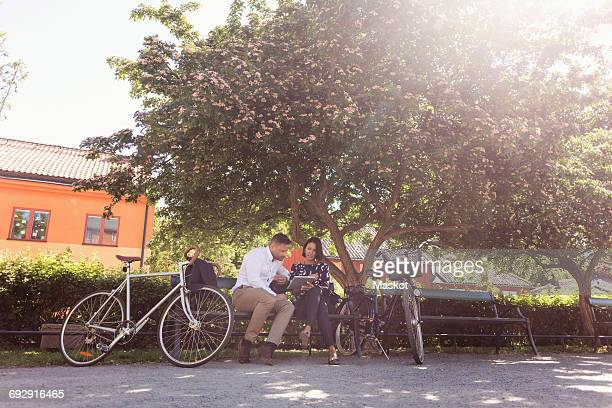 Business people using digital tablet while sitting on park bench by bicycles