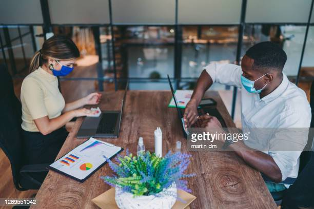 business people using disinfection wipes during covid-19 - antiseptic wipe stock pictures, royalty-free photos & images