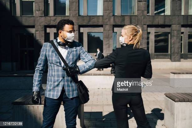 business people using elbow greeting during covid-19 pandemic - elbow bump stock pictures, royalty-free photos & images
