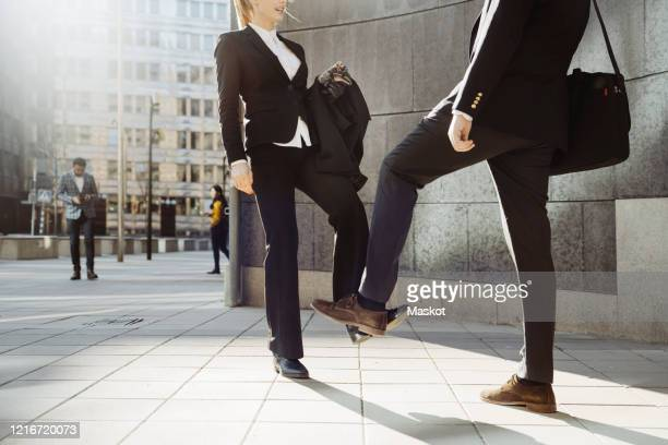 business people using feet greeting during covid-19 pandemic - handshake stock pictures, royalty-free photos & images