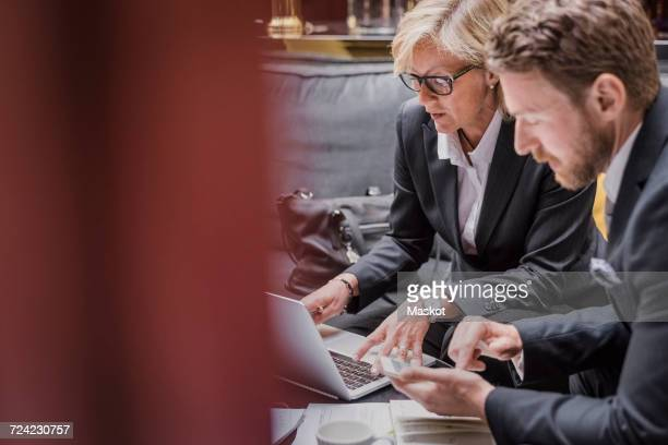 Business people using laptop and mobile phone during meeting in hotel reception