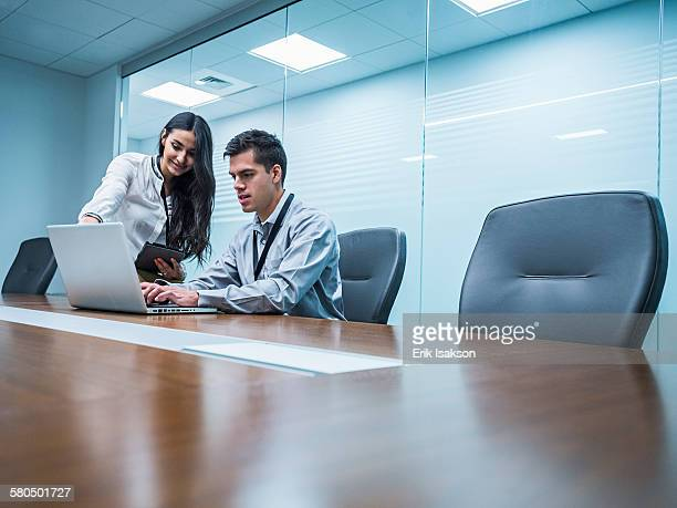 Business people using laptop in conference room