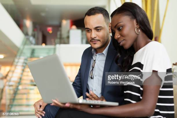 Business people using laptop in hotel lobby