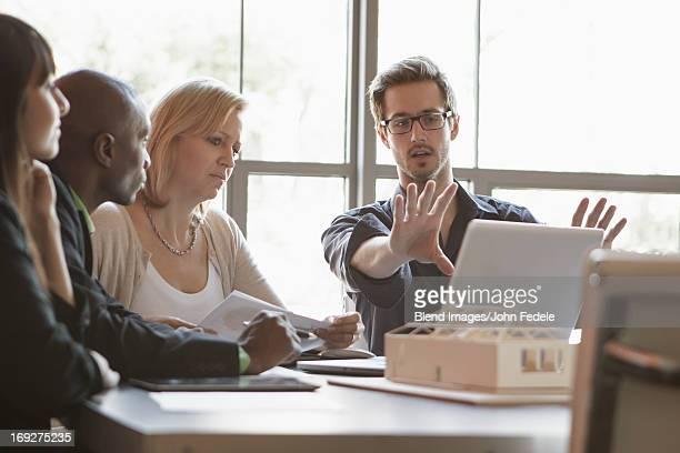 business people using laptop in meeting - persuasão - fotografias e filmes do acervo