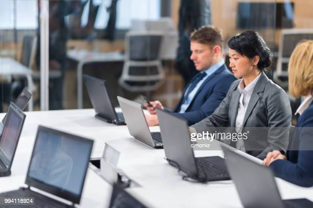 business people using laptop - blue blazer stock pictures, royalty-free photos & images