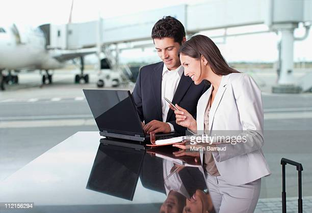 Business people using laptop together at airport