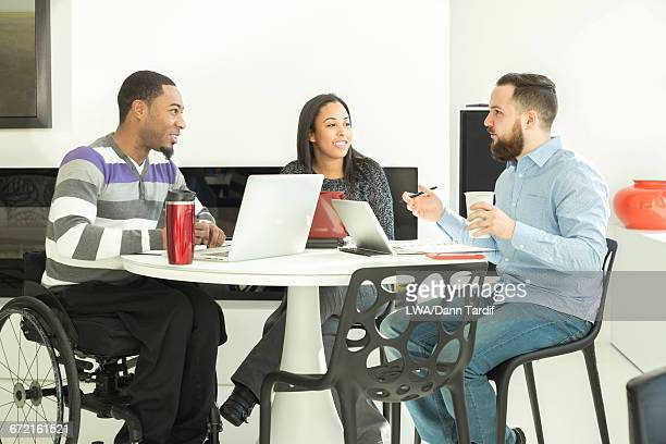 business people using laptops at table - multiculturalism stock pictures, royalty-free photos & images