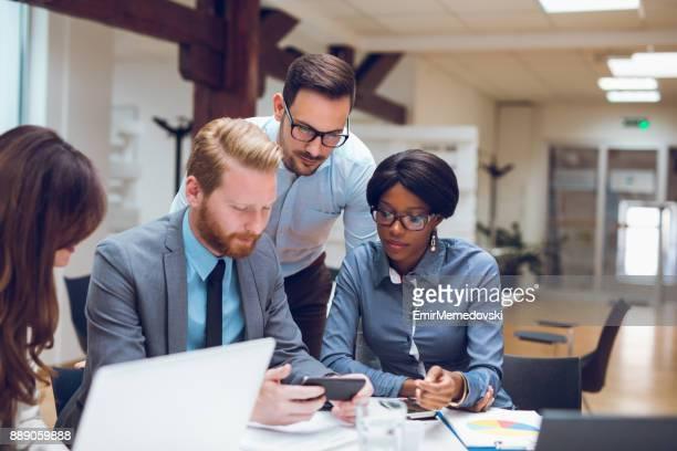Gens d'affaires à l'aide de téléphones mobiles au cours de la réunion d'affaires