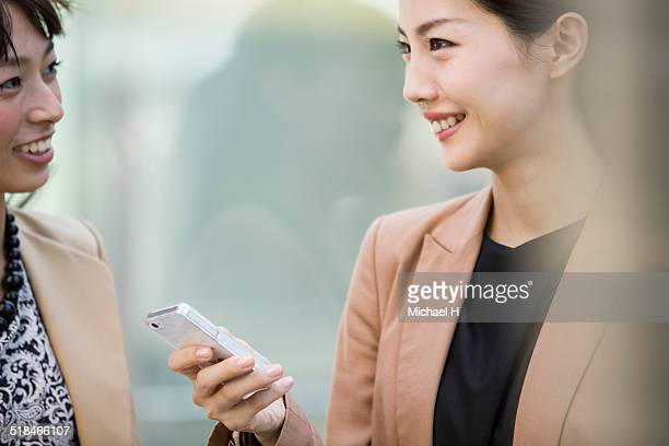 Business people using smart phone outdoors