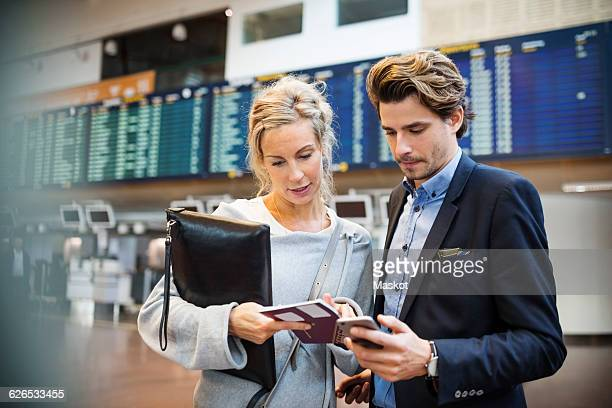 Business people using smart phone while looking at passport in airport