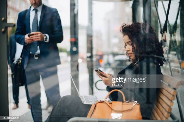 Business people using smart phones while waiting at bus shelter seen from glass