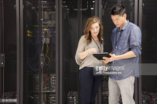 Business people using tablet computer in server room