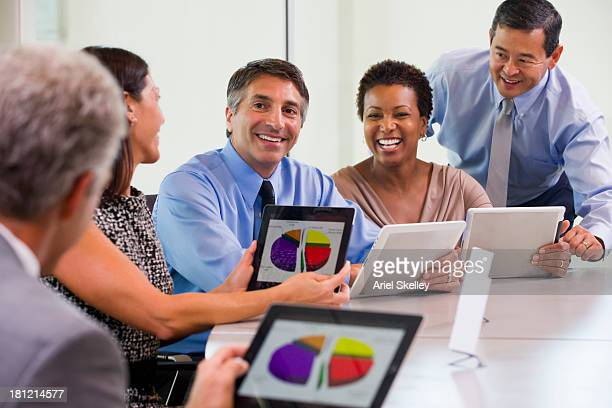 business people using tablet computers in meeting - multiculturalismo foto e immagini stock