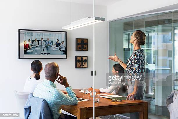 business people video conferencing in board room - computermonitor stockfoto's en -beelden