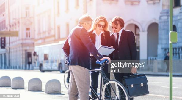 business people waiting at bus station - bicycle parking station stock photos and pictures