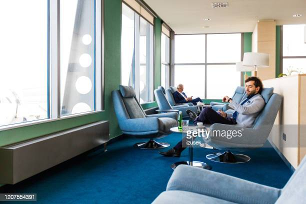 empresários esperando por voo no lounge vip do aiport - izusek - fotografias e filmes do acervo