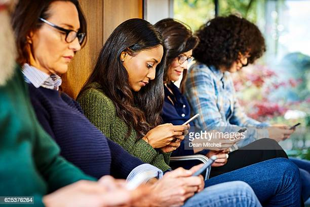 Business people waiting for interview in office using mobile phones