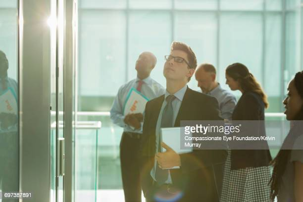 Business people waiting for lift in office atrium