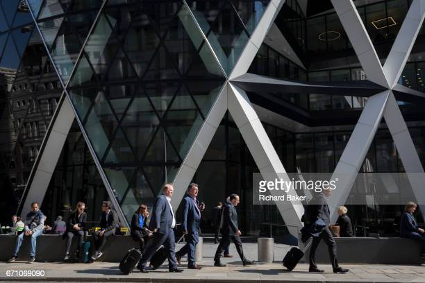Business people walk beneath the architectural struts of the Swiss Re at 30 St Mary Axe in the City of London the capital's financial district also...