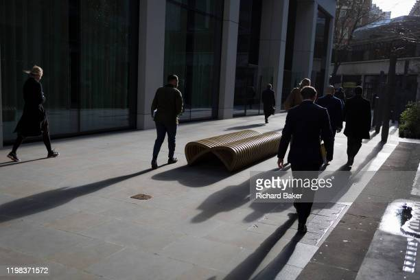 Business people walk down a pedestrian path between mainly insurance and financial businesses in the City of London the capital's financial district...