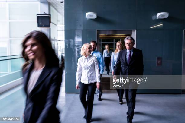 business people walk out of the lift in the lobby. - medium group of people stock pictures, royalty-free photos & images