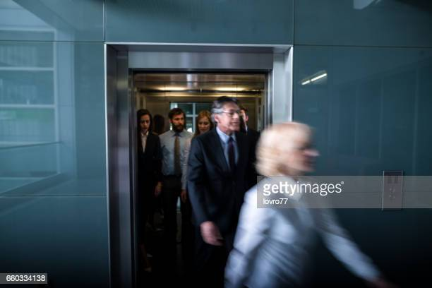 Business people walk out of the lift in the lobby.