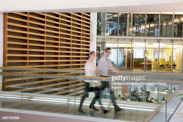 Business people walking along elevated walkway