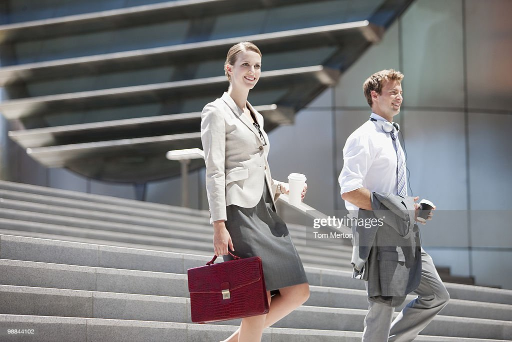 Business people walking down steps outdoors : Stock Photo