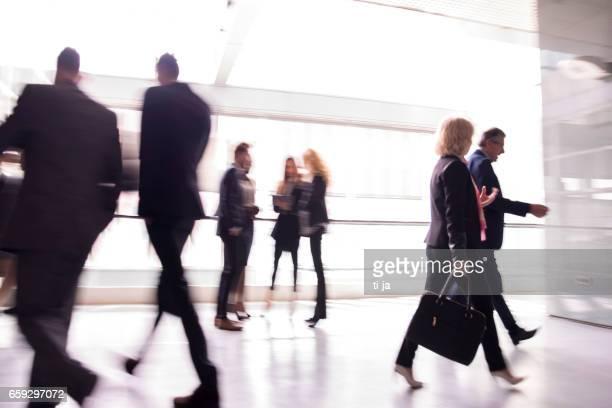 Geschäftsleute, die die Halle hinunterlaufen