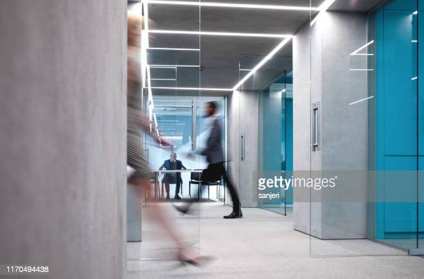 business people walking down the hallway - immagine mossa foto e immagini stock