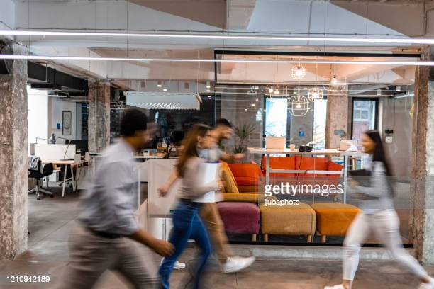 business people walking down the hallway - huddle stock pictures, royalty-free photos & images