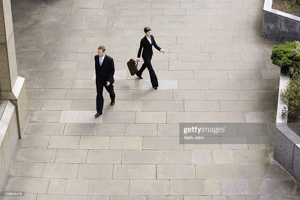 Business people walking in courtyard : Stock Photo