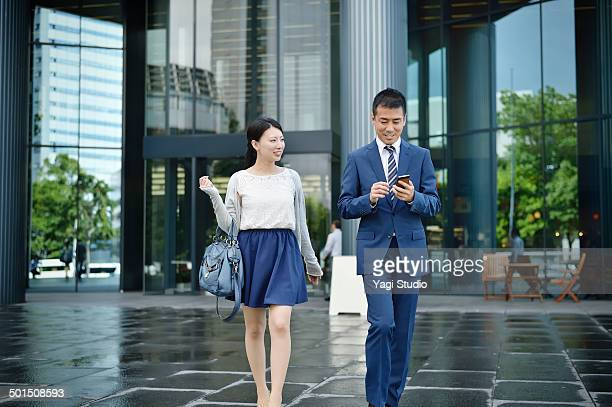Business people walking in front of building
