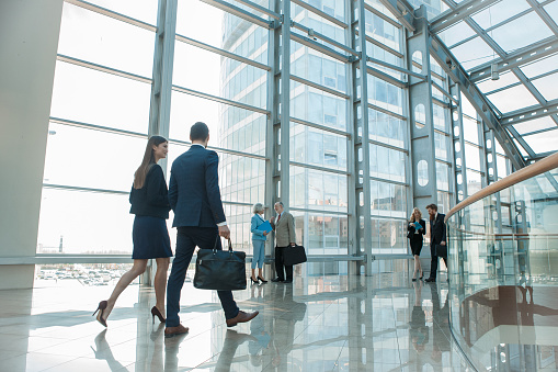 Business people walking in glass building 806982598