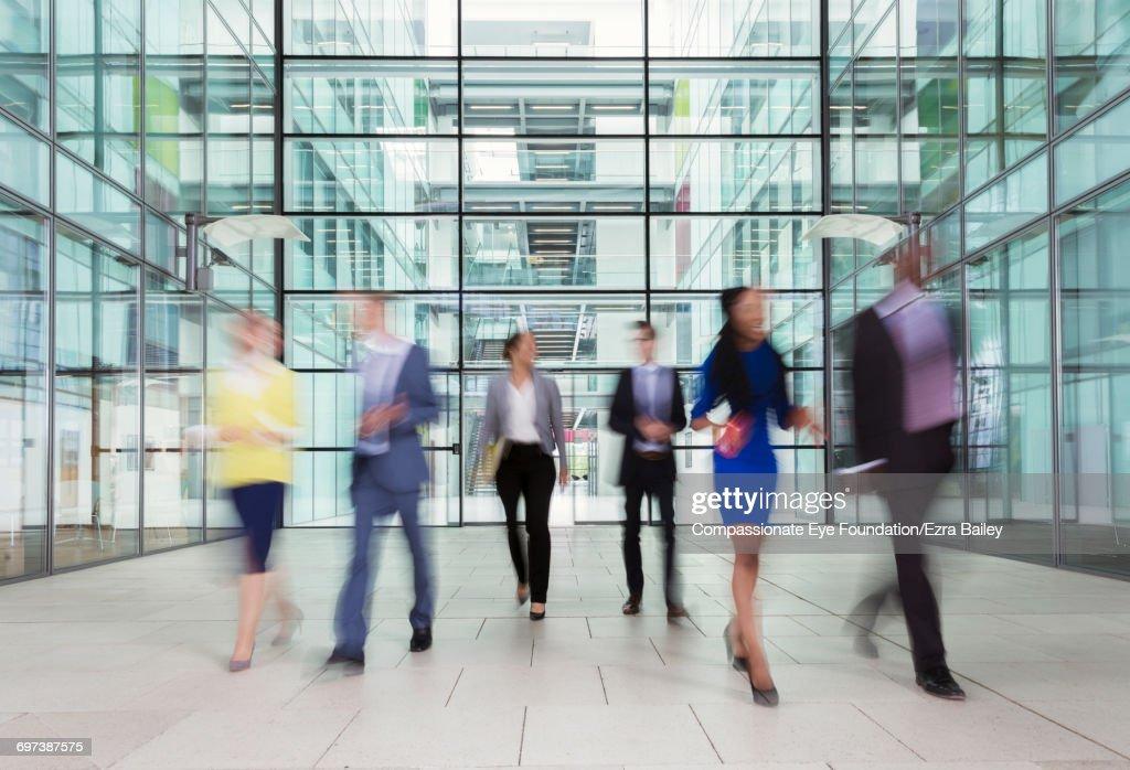 Business people walking in modern lobby : Stock-Foto