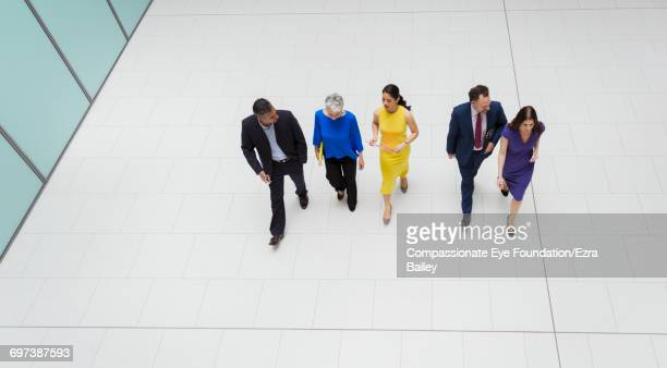 Business people walking in modern lobby
