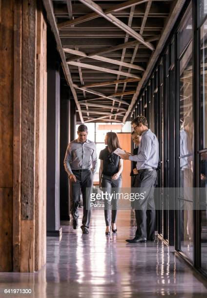 Business people walking in office corridor