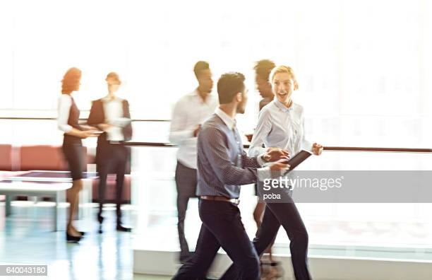 business people walking in office lobby - motion blur stock photos and pictures