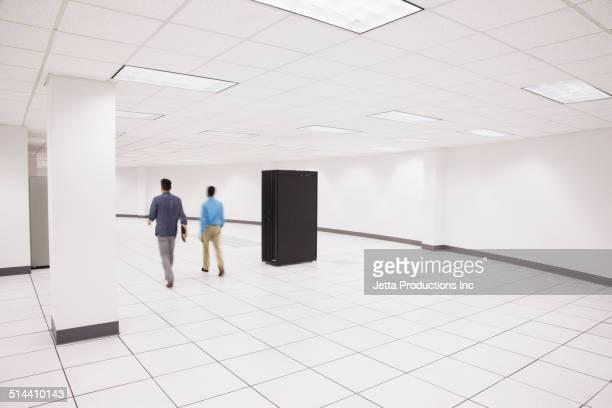 Business people walking in server room