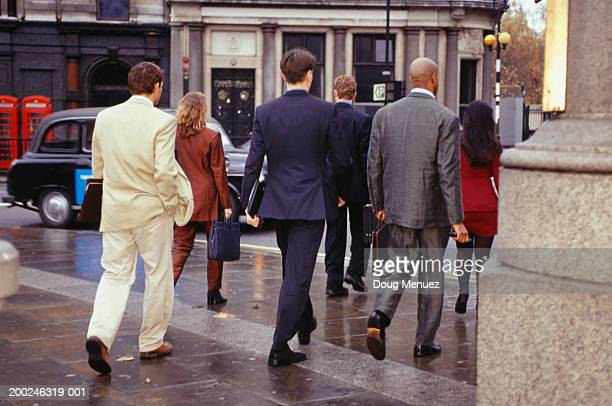 Business people walking in street, London