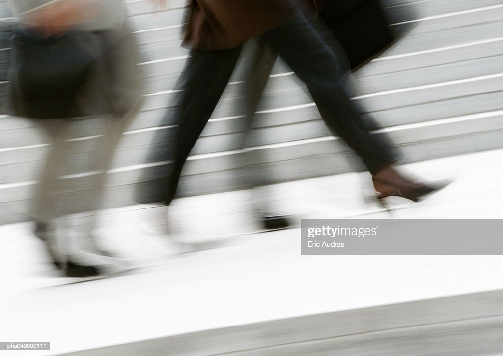 Business people walking in street, low section, blurred : Photo