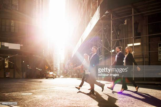 business people walking on city street by buildings during sunny day - wall street stock-fotos und bilder