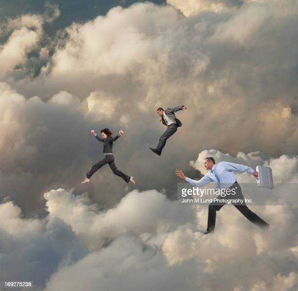 Business people walking on clouds
