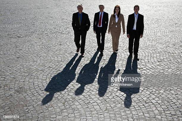 Business people walking on cobbled road