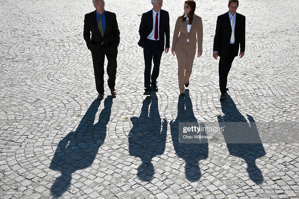 Business people walking on cobbled road : Stock Photo