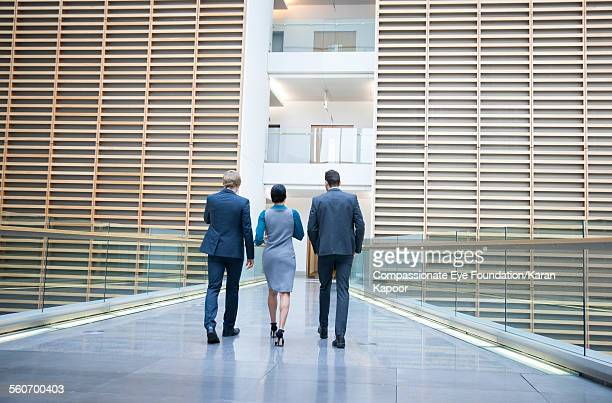 business people walking on office balcony - three people stock pictures, royalty-free photos & images