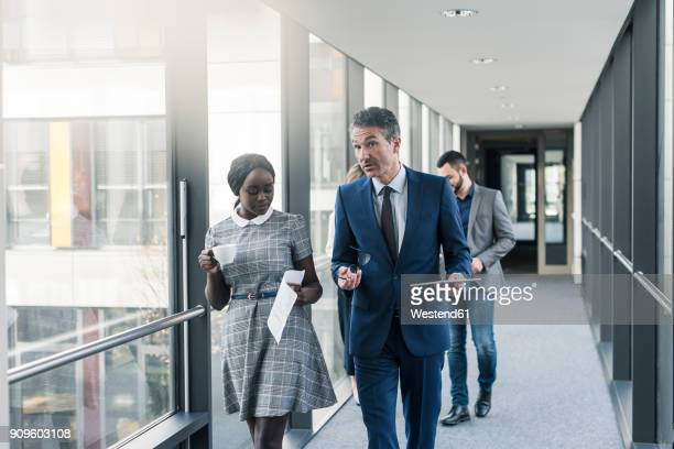 business people walking on office floor - four people stock pictures, royalty-free photos & images