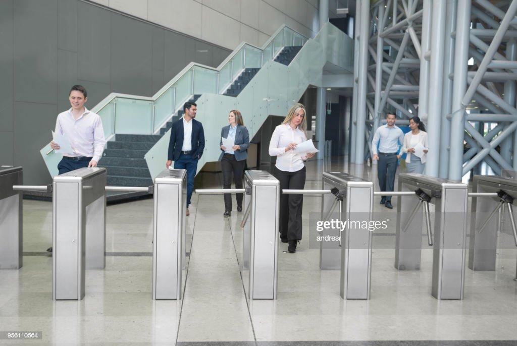 Gente de negocios caminar fuera de un centro de negocios, pasando por los torniquetes de acceso : Foto de stock